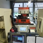 ... a control unit for one of the CNC machines, in the background another wire-cut EDM